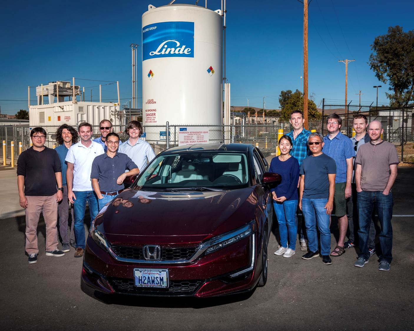 LLNL researchers stand next to a fuel cell vehicle with H2AWSM on the license plate